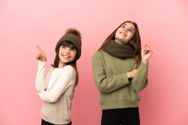 좋은 아이디어를 가리키고 올려 분홍색 배경에 고립 된 겨울 옷을 입고 작은 자매