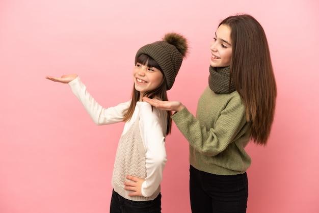 Маленькие сестры в зимней одежде на розовом фоне, указывая назад и представляя продукт