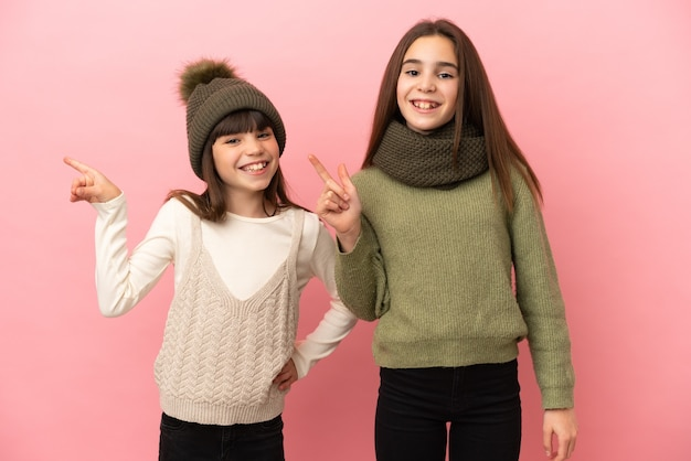Маленькие сестры в зимней одежде на розовом фоне, указывая пальцем в сторону и представляя продукт