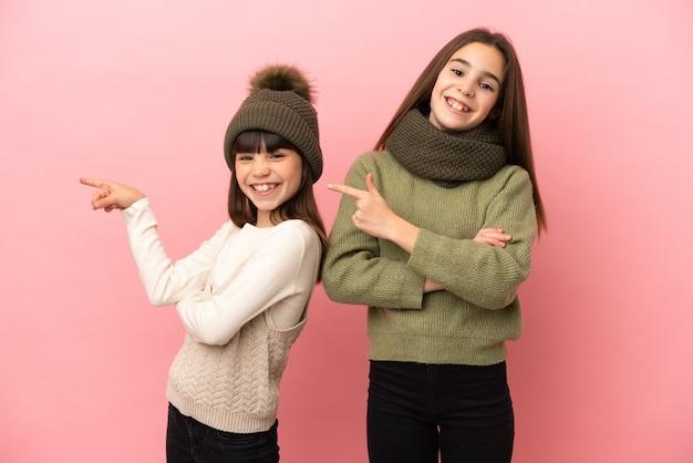 Маленькие сестры в зимней одежде на розовом фоне, указывая пальцем в сторону в боковом положении