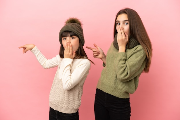 분홍색 배경에 격리된 겨울 옷을 입은 어린 자매들은 놀란 얼굴로 옆으로 손가락을 가리키고 있다