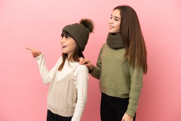 Маленькие сестры в зимней одежде на розовом фоне, указывая в сторону, чтобы представить продукт