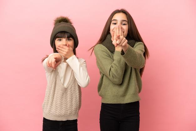 Маленькие сестры в зимней одежде, изолированные на розовом фоне, указывая пальцем на кого-то и смеясь