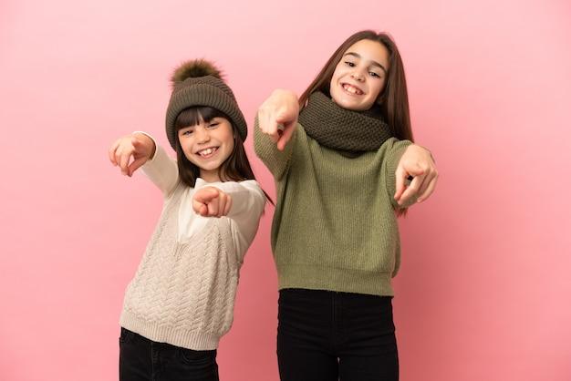 Маленькие сестры в зимней одежде на розовом фоне указывают пальцем на вас, улыбаясь