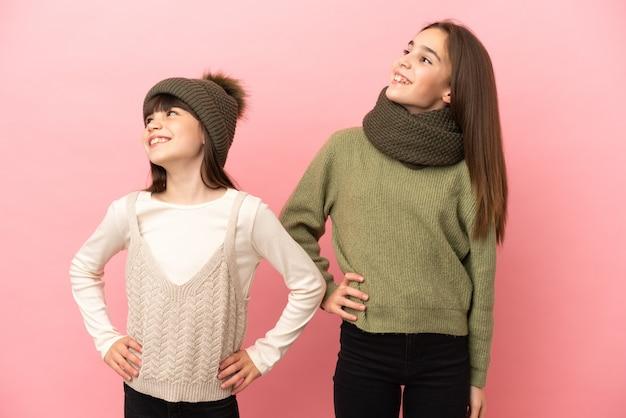 Маленькие сестры в зимней одежде, изолированные на розовом фоне, позируют с руками на бедрах и смеются