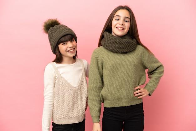 Маленькие сестры в зимней одежде, изолированные на розовом фоне, позируют с руками на бедрах и улыбаются