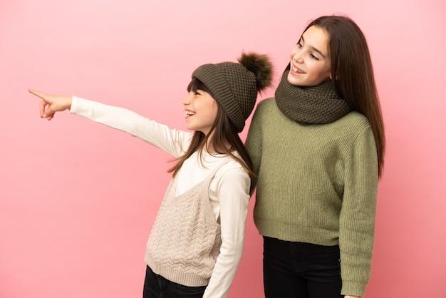 Маленькие сестры в зимней одежде, изолированные на розовом фоне, представляя идею, улыбаясь в сторону
