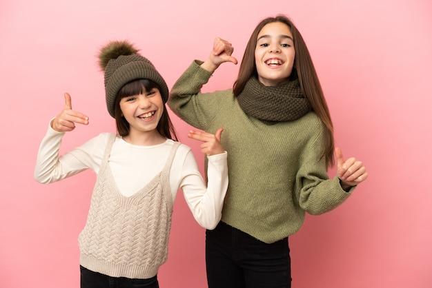 Маленькие сестры в зимней одежде, изолированные на розовом фоне, гордые и самодовольные в любви к себе.
