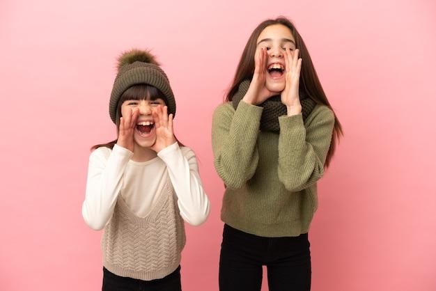 Маленькие сестры в зимней одежде на розовом фоне кричат и что-то объявляют