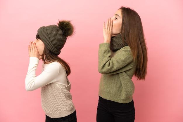 분홍색 배경에 고립 된 겨울 옷을 입고 작은 자매는 옆으로 입 벌리고 외치는 소리