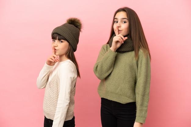 Маленькие сестры в зимней одежде изолированы на розовом фоне, показывая знак закрывающегося рта и жест молчания