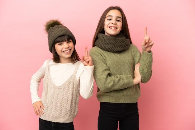 Маленькие сестры в зимней одежде на розовом фоне показывают и поднимают палец в знак лучших