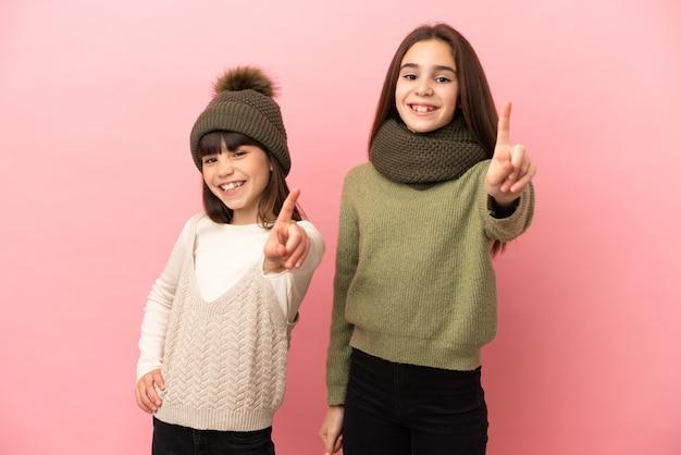 Маленькие сестры в зимней одежде на розовом фоне, показывая и поднимая палец