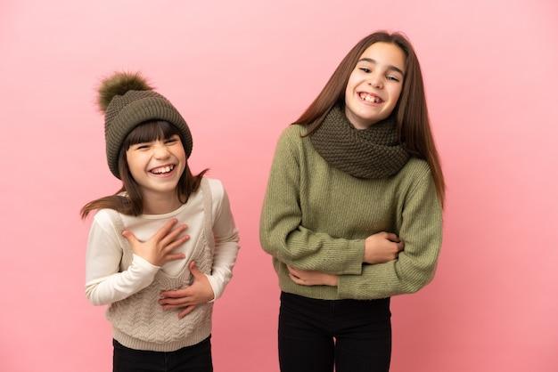 Маленькие сестры в зимней одежде на розовом фоне много улыбаются, кладя руки на грудь