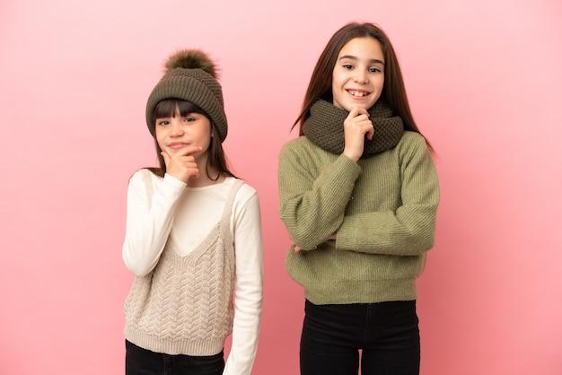 Маленькие сестры в зимней одежде, изолированные на розовом фоне, улыбаются и смотрят вперед с уверенным лицом