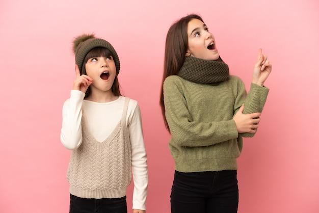 분홍색 배경에 격리된 겨울 옷을 입은 어린 자매들은 손가락을 가리키는 아이디어를 생각하고 있다