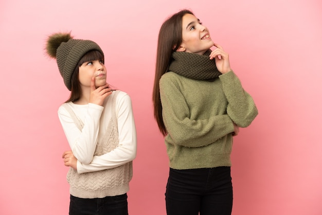 見上げながらアイデアを考えてピンクの背景に分離された冬の服を着ている妹