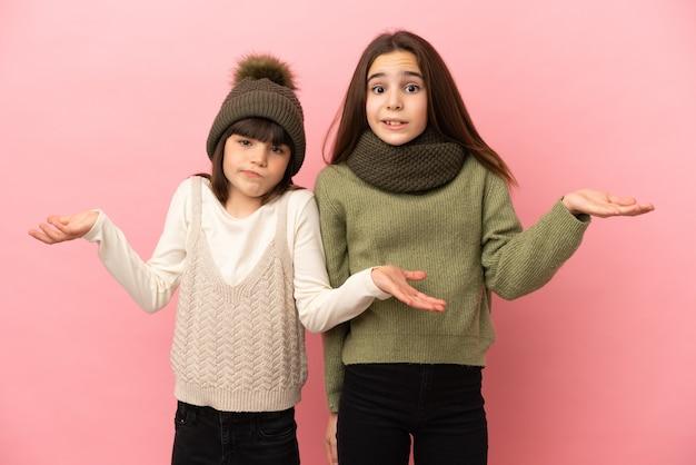 Маленькие сестры в зимней одежде на розовом фоне недовольны и разочарованы чем-то, потому что чего-то не понимают