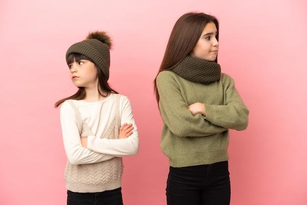 물린 입술 동안 혼란 얼굴 표정으로 분홍색 배경에 고립 된 겨울 옷을 입고 작은 자매