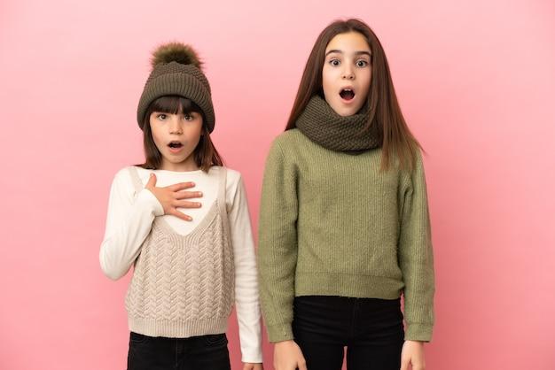 Маленькие сестры в зимней одежде изолированы на розовом фоне с удивленным и шокированным выражением лица