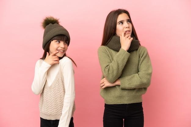 Маленькие сестры в зимней одежде изолированы
