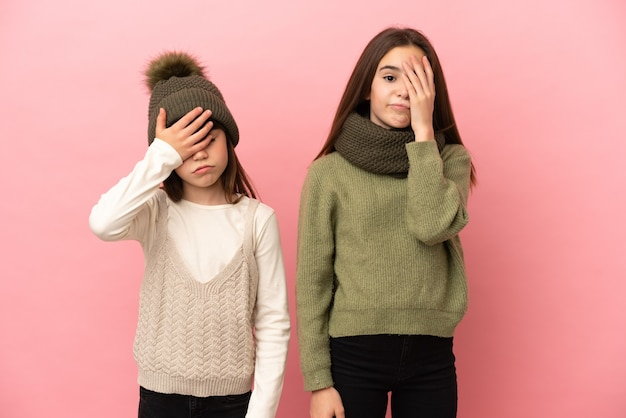 Little sisters wearing a winter clothes isolated