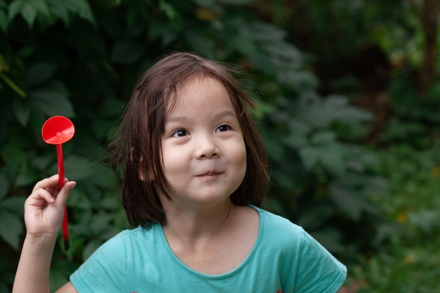 Маленькая шестилетняя девочка стреляет из игровой стрелы в цель