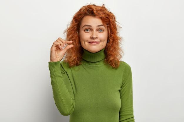 Concetto di piccole dimensioni. la bella giovane femmina dai capelli rossi lieta modella qualcosa di piccolo
