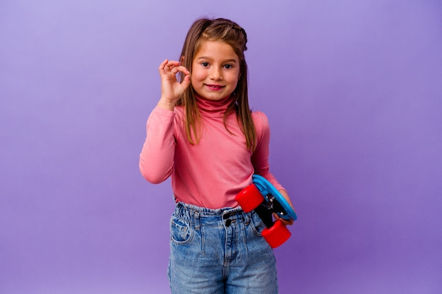 Little skater caucasian girl isolated on blue background cheerful and confident showing ok gesture.