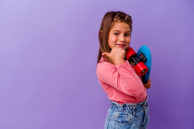 Little skater caucasian girl isolated on blue background points with thumb finger away, laughing and carefree.
