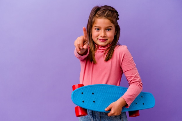 Little skater caucasian girl isolated on blue showing number one with finger.