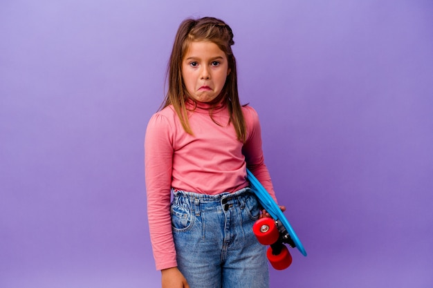 Little skater caucasian girl isolated on blue wall shrugs shoulders and open eyes confused.