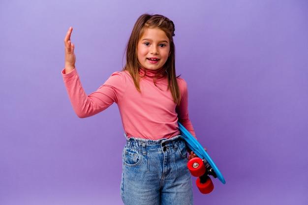 青い背景に孤立した小さなスケーター白人の女の子は、嬉しい驚きを受け取り、興奮し、手を上げます。