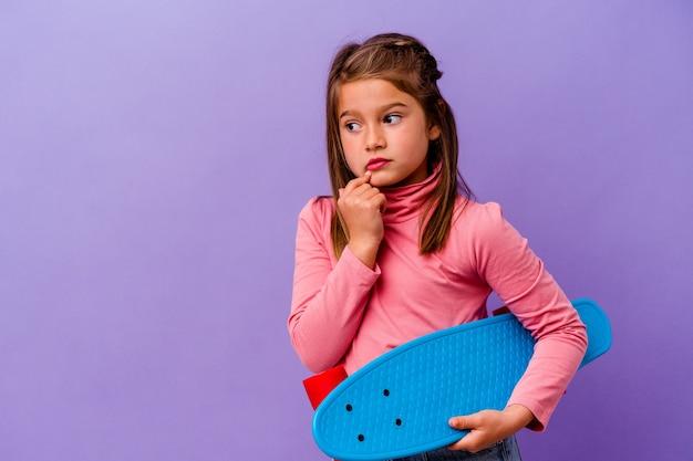 青い背景に隔離された小さなスケーター白人の女の子は、コピースペースを見ている何かについて考えてリラックスしました。