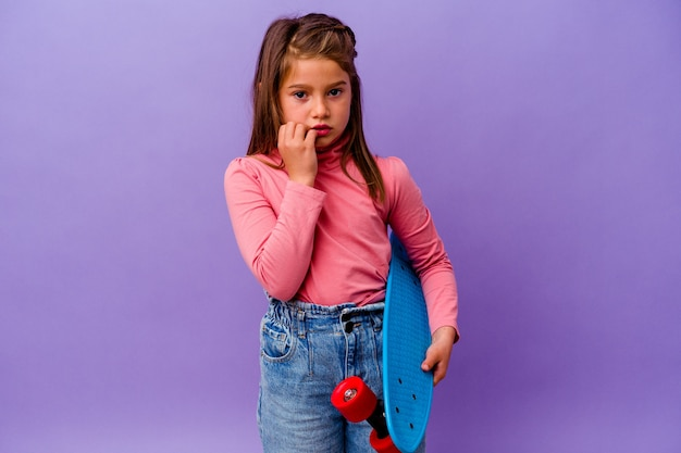 Маленькая девочка конькобежца кавказская изолирована на синих кусающих ногтях, нервничает и очень тревожится.