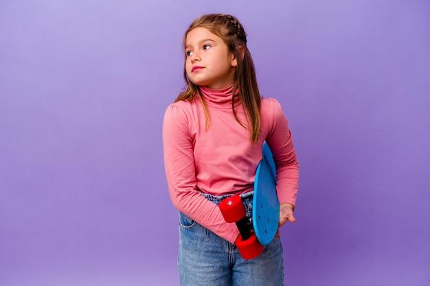 목표와 목적을 달성하는 꿈을 꾸고 파란색 벽에 고립 된 작은 스케이팅 백인 소녀