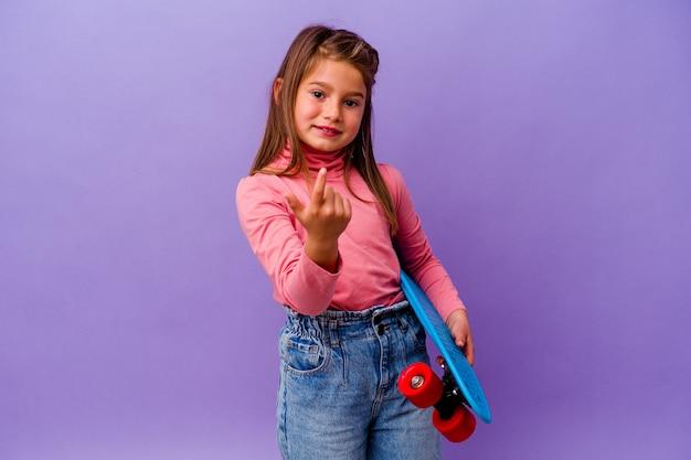 당신을 손가락으로 가리키는 파란색 벽에 고립 된 작은 스케이팅 백인 소녀 초대 가까이 와서.