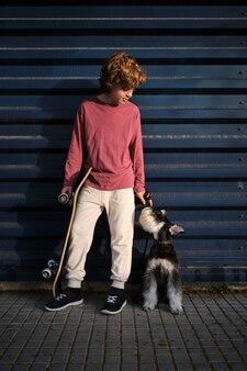 通りで休んでいる犬と小さなスケーター