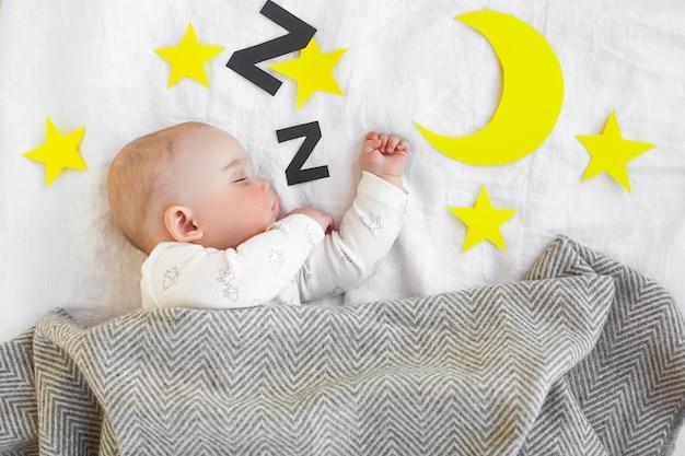 ベッドで少し眠そうな子供。眠っているかわいい赤ちゃん