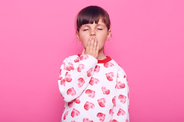 Little sleepy female child keeping eyes closed, covering mouth with palm while yawning, wearing white jumper with hearts, isolated over pink wall.