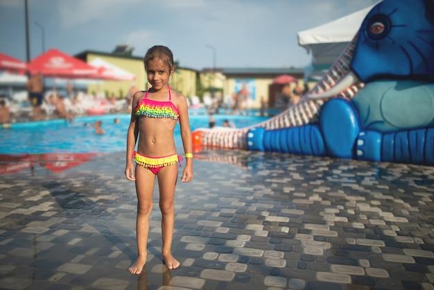밝은 수영복에 작은 슬림 귀여운 소녀가 따뜻한 야외에서 어린이 워터 존을 배경으로 포즈를 취합니다.