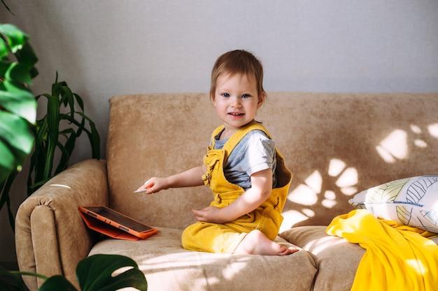 タブレットとペンスタイラスを備えたソファの上の小さな小さな幼児