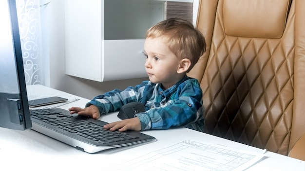 Little smart toddler boy sitting in office and working on computer.