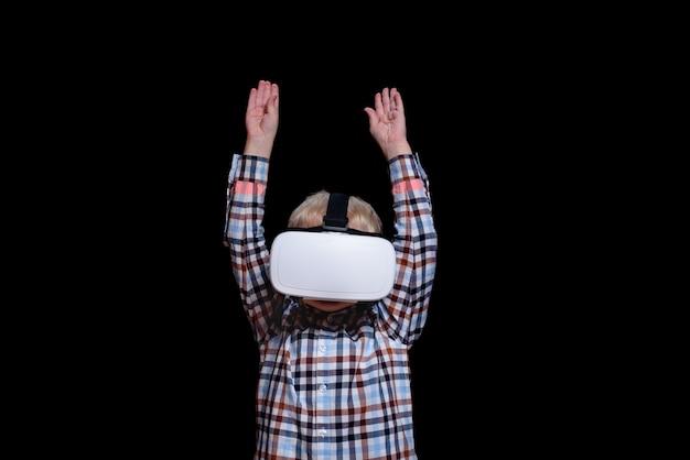 Маленький улыбающийся мальчик в очках виртуальной реальности с поднятыми руками
