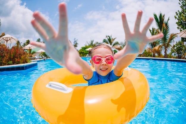 Маленькая улыбка девушка в открытом бассейне