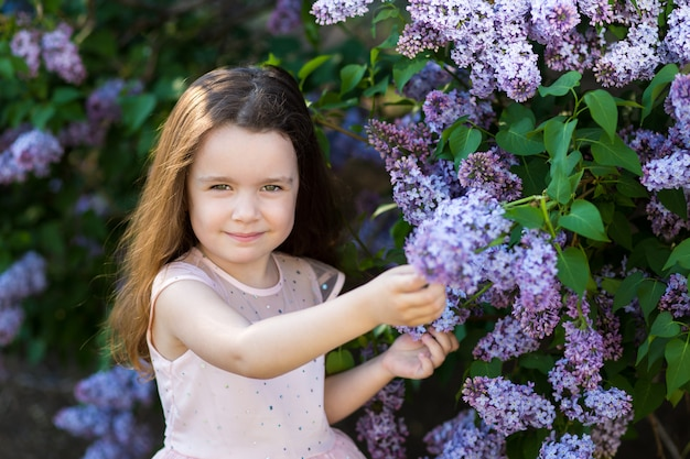 A little smile girl is in the lilac bushes in the sunset garden, spring blooming park.