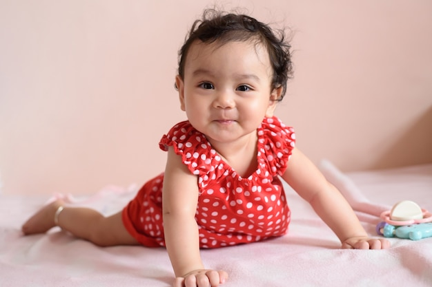 Маленький улыбающийся азиатский ребенок, одетый в красное, тренируется ползать по кровати с пастельным фоном
