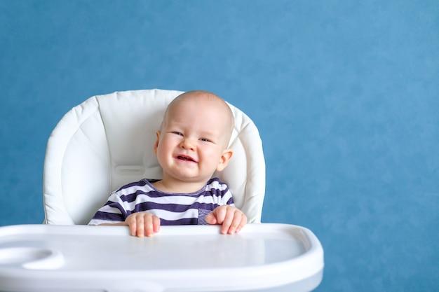 Маленькая улыбающаяся девочка на стульчике у себя дома