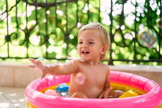 웃고 있는 작은 아기는 작은 팽창식 수영장에 앉아 비누 거품을 잡는다