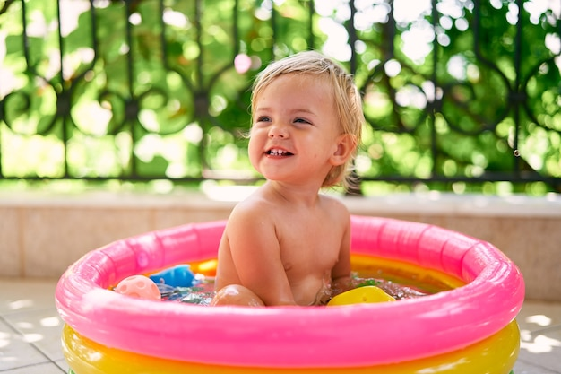 작은 풍선 수영장에 앉아 웃는 아기